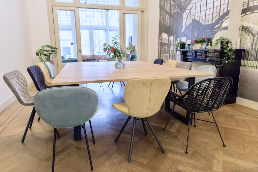 Eiken tafel en planten en bloemen en behang van station den bosch bij vergaderruimte de salon in den bosch met gele stoelen en blauwe stoelen en grijze stoelen en zwarte stoelen