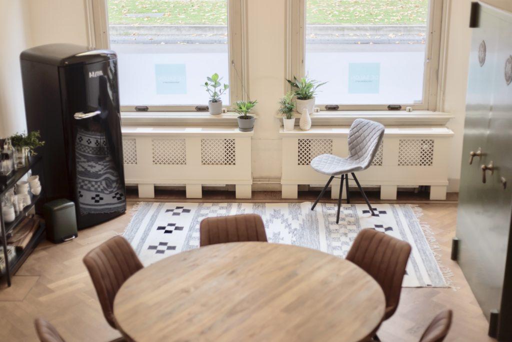 Ronde tafel met bruine leren stoelen en grijze stoel en zwarte koelkast en planten en kleed in vergaderruimte de salon in den bosch