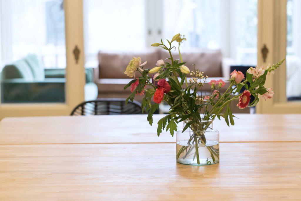 Bloemen in vaas op eiken tafel met zwarte stoel in vergaderruimte de salon in den bosch