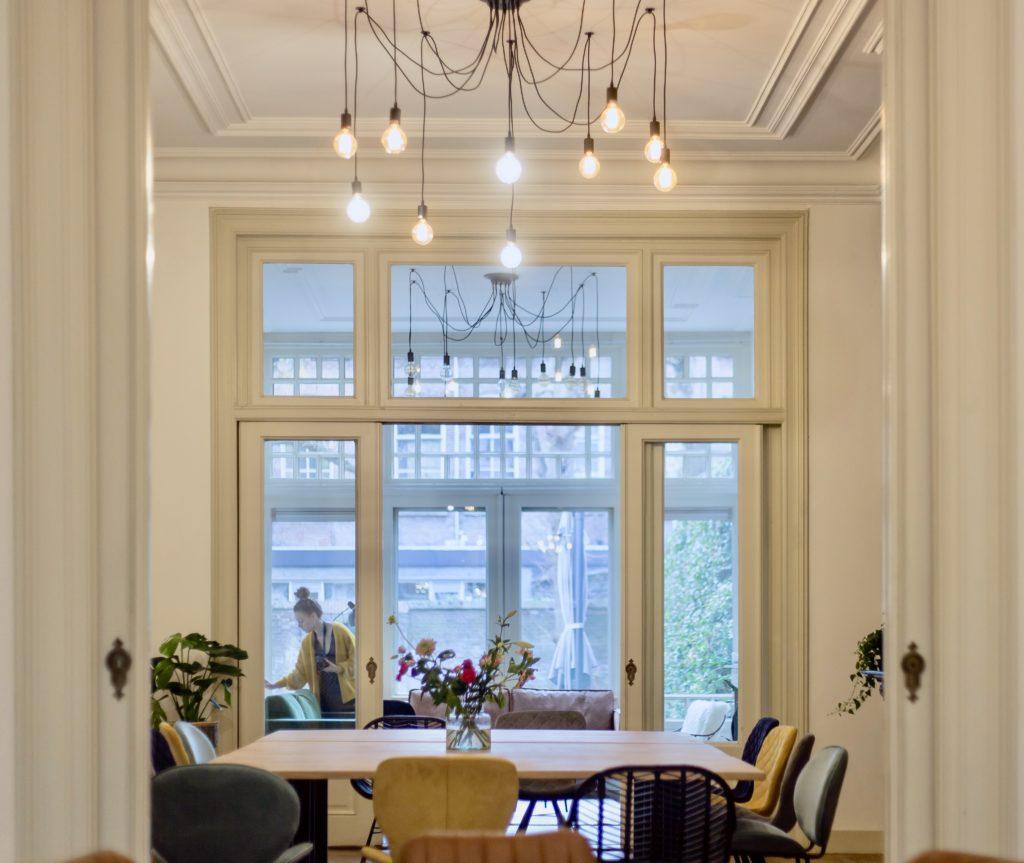 Bloemen in vaas op eiken tafel met zwarte stoel in vergaderruimte de salon in den bosch met bruine leren bank en groene plant en gele stoel