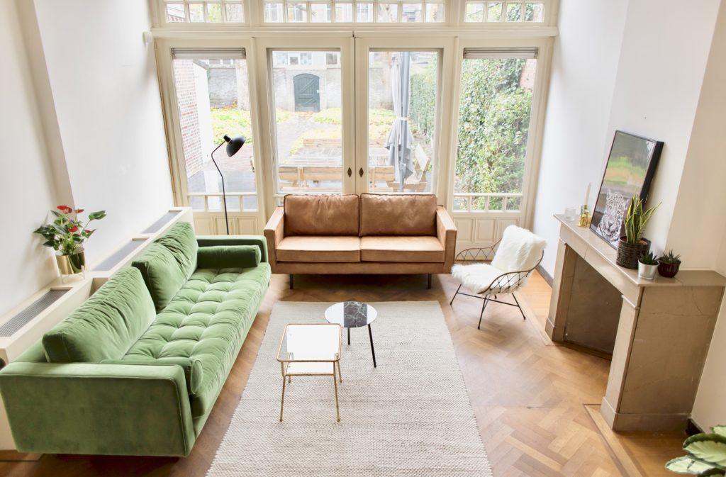 Groene bank en bruine leren bank en wit kleed en planten in zuitruimte van vergaderruimte de salon in den bosch