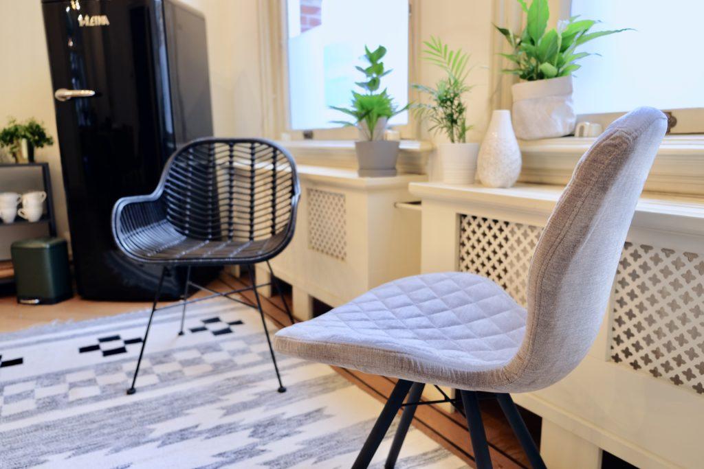Een grijze stoel, een zwarte stoel, planten en een koelkast in vergaderruimte de salon in den bosch